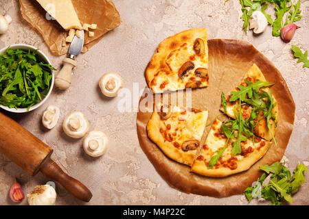 Pizza aux légumes avec des ingrédients sur fond de vieilles pierres. Pizza au fromage champignons et roquette. Pizza Banque D'Images