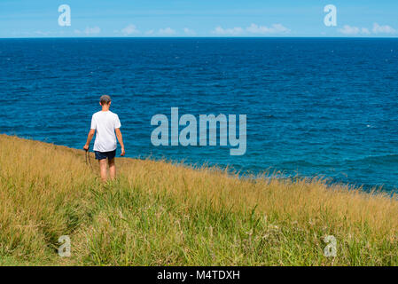 Un jeune homme marchant le long d'un étroit chemin à travers la longue herbe près de l'océan avec un appareil photo Banque D'Images