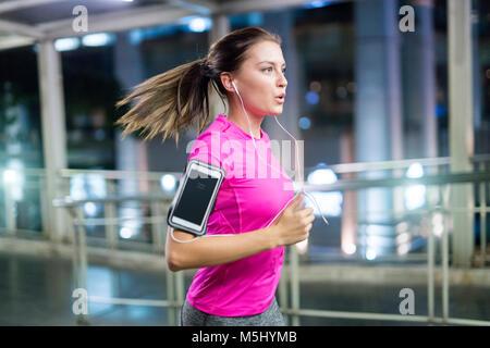 Jeune femme en rose sportshirt fonctionnant en ville la nuit Banque D'Images