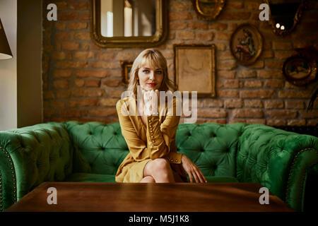 Portrait de femme élégante assise sur un sofa Banque D'Images