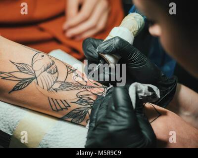 Tatoueur au travail. Woman in Black tatouage gants en latex d'un jeune homme à la main avec image colorée en studio. Banque D'Images