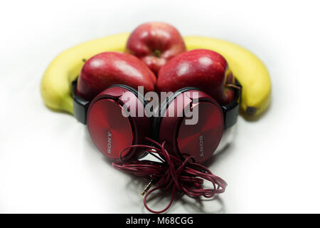 Pommes rouges et de bananes avec écouteurs Sony rouge sur fond blanc (la musique est la nourriture pour l'âme) Banque D'Images