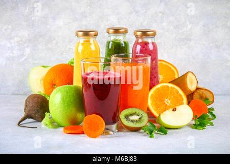 Vert, jaune, violet smoothies en bouteilles de cassis, persil, pommes, kiwi, orange gris sur une table. Smoothies Banque D'Images