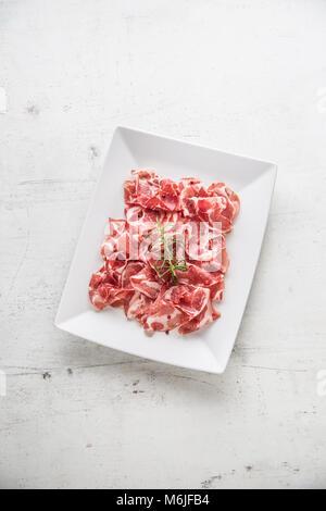 Le prosciutto. Gondolé tranches de prosciutto italien délicieux avec le romarin. Banque D'Images