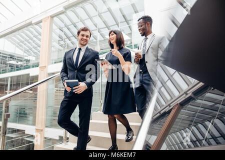 Trois hommes d'affaires multiraciale en descendant les escaliers avec digital tablet Banque D'Images