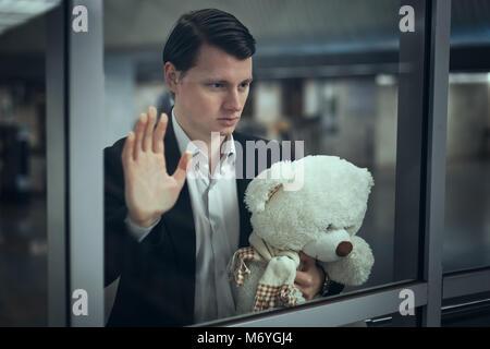 Jeune homme regarde par la fenêtre et attend une réunion. Il a un ours en peluche dans ses mains Banque D'Images
