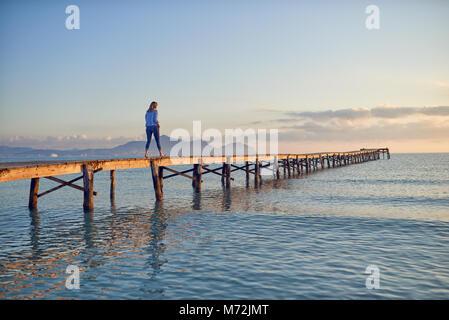 Femme marche loin de la caméra le long d'une jetée en bois ou promenade au coucher du soleil sur une mer calme avec Banque D'Images