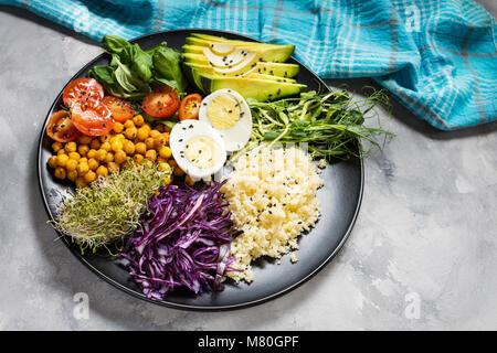 Bol déjeuner végétalien sain. Bol bouddha vegan. Les légumes et les noix dans le bol bouddha sur fond de béton Banque D'Images