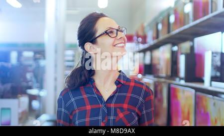 Belle Jeune femme entre dans le magasin d'électronique avec étagères Navigation Derniers modèles de téléviseur UHD Banque D'Images