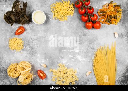Diverses matières premières et ingrédients pour la cuisson des pâtes (tomates, huile d'olive, ail) sur fond gris. Banque D'Images