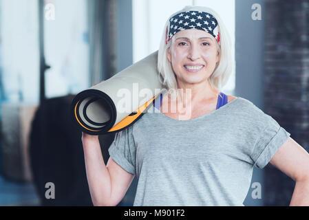 Belle Dame senior avec mat qui pose pour appareil photo Banque D'Images