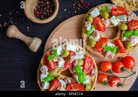 Apéritif italien Friselle. Pain italien avec des tomates séchées Friselle cerise, fromage mozzarella, olives, thon, le basilic et le poivre dans un pilon. Il Banque D'Images
