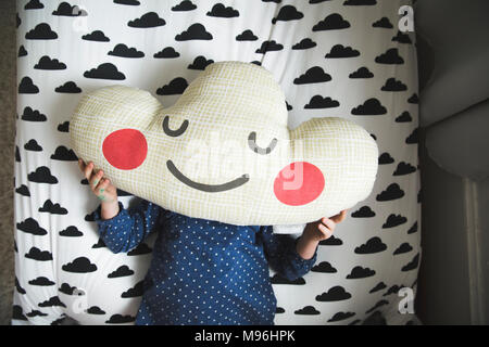 Girl laying on bed with cloud oreiller sur son visage Banque D'Images