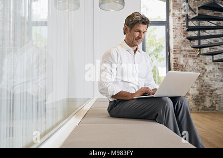 Businessman sitting on bench in modern office using laptop Banque D'Images