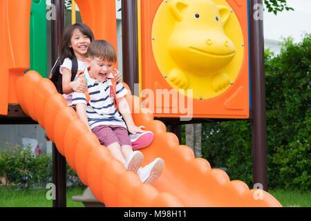 Deux jeunes amis s'amusant à jouer ensemble sur la diapositive à l'école,aire d'activité Retour à l'école Banque D'Images