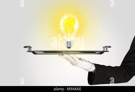 Au service d'une idée d'affaires brillant concept en utilisant une ampoule à lumière jaune chaud mousseux lumineux présenté sur une plaque d'argent Banque D'Images