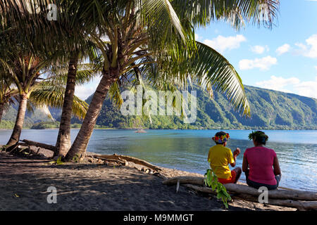 Deux femmes avec gerbe de fleurs assis sous les palmiers sur le tronc de l'arbre, près de la côte, Taurea Tahiti Iti, iles de la société Banque D'Images