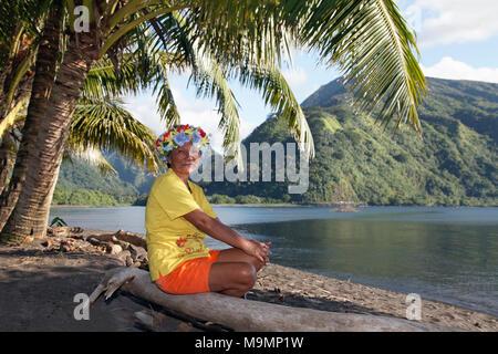 Vieille Femme avec gerbe de fleurs assis sous les palmiers sur le tronc de l'arbre, près de la côte, Taurita Tahiti Iti, iles de la société Banque D'Images