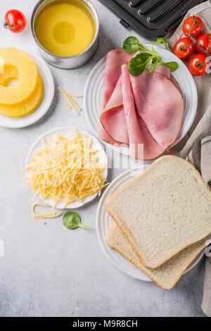 Ingrédients pour faire des toasts grillés sandwich hawaii avec jambon, ananas, tomate et fromage. L'été en bonne santé food concept avec de l'espace libre pour le texte. Banque D'Images