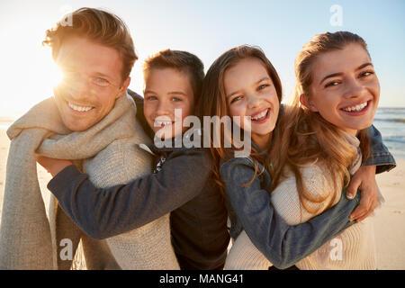 Les parents qui permet aux enfants des promenades sur la plage d'hiver de ferroutage Banque D'Images