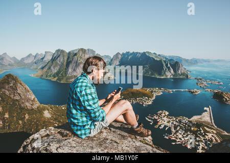 L'homme à l'aide de voyageurs assis sur des montagnes smartphone haut Voyager concept de vie en plein air d'aventure Reinebringen mountain Vue aérienne des îles Lofoten Banque D'Images