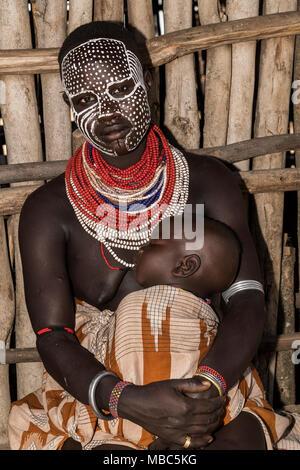 Jeune femme avec visage peint et bébé, tribu Karo, Nationalités et Peuples du Sud, l'Éthiopie Région' Banque D'Images