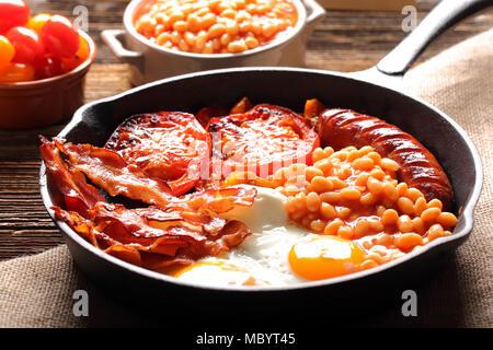 Petit déjeuner anglais avec des saucisses, des tomates grillées, des œufs, du bacon et des haricots sur le poêle. Banque D'Images