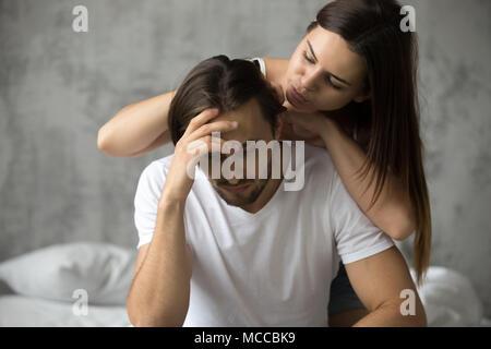 Caring woman embracing contrarié offensé homme essayant de faire la paix lui remonter, épouse aimante mari de ressentiment s'excuser après un conflit d'excuser de demander Banque D'Images