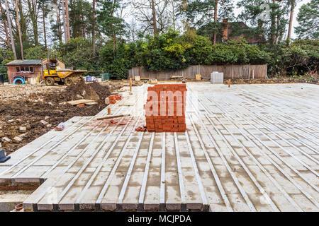 Tas de briques rouges typiques chambre empilés sur une habitation neuve construite en partie l'aménagement intercalaire le site de construction dans le sud-est de l'Angleterre, Surrey, UK Banque D'Images