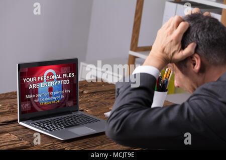 Close-up de l'homme d'affaires à la recherche à l'écran de l'ordinateur portable montrant les fichiers personnels d'un texte chiffré Banque D'Images
