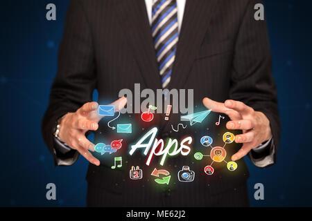 Businessman with dessiné les icônes d'application et de symboles dans ses mains Banque D'Images