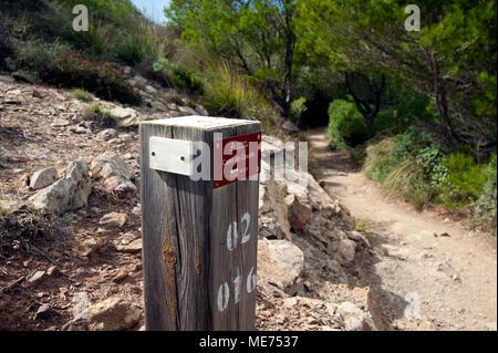 Un panneau en bois indiquant le chemin derrière sur la Cami de Cavalls promenade côtière à Minorque espagne Banque D'Images