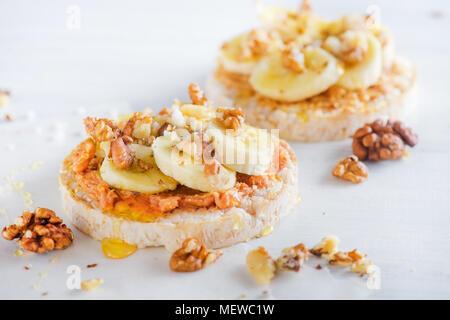 Crisp pain aux bananes et beurre d'arachide snack. Petit-déjeuner sain avec des noix et du miel. High key concept de régime. Banque D'Images