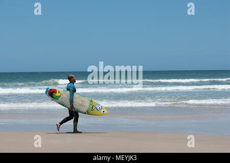 Male surfer carrying surfboard, portant un corps entier wet suit la marche sur la plage de Praia do Rosa, Brésil. Banque D'Images