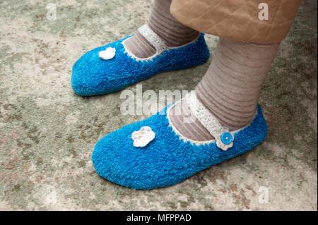 Femme âgée portant des chaussettes et des chaussons pour garder au chaud et confortable en hiver parution modèle Banque D'Images