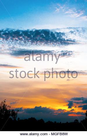 Un coucher de soleil sur un jour nuageux en saison des pluies. Voir les couleurs saturées. Banque D'Images