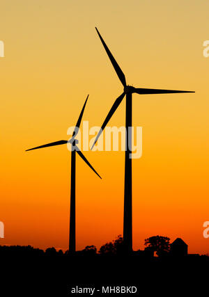 Deux éoliennes en silhouette au coucher du soleil. Banque D'Images