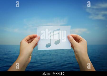 Femme mains tenant une feuille de papier avec une note de musique à l'intérieur, sur fond bleu horizon de mer. L'écoute au rythme des vagues de l'océan. Banque D'Images