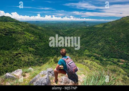 Caucasian hiker homme prendre un repos sur sommet de montagne avec sac à dos. Banque D'Images