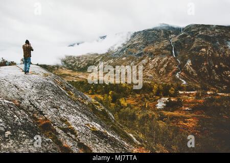 L'homme seul voyageur sur falaise forêt brumeuse montagne aventure voyage paysage concept de vie vacances scandinaves en Norvège Banque D'Images