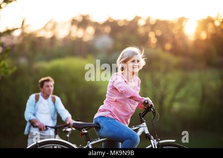 Beau couple avec des bicyclettes à l'extérieur au printemps la nature. Banque D'Images