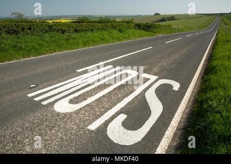 Un lent signe sur le front d'une colline sur une route à travers la campagne du Dorset qui mène dans la distance à Dorchester, dans le Dorset England UK. Le 7 mai 2018 Banque D'Images
