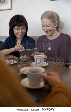 Souriant, senior women friends using digital tablet at cafe Banque D'Images