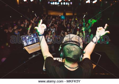 DJ enthousiaste sur scène désignant foule in nightclub Banque D'Images