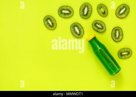 Beaux art fond alimentaire. En bouteilles en verre de jus vert tranches de kiwi sur la surface d'un vert vif. Banque D'Images