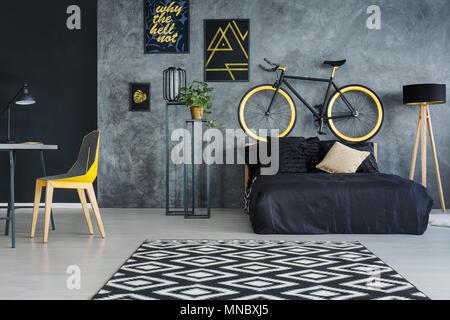 Gray salle multifonctionnelle avec lit, bureau, chaise et décoration murale Banque D'Images
