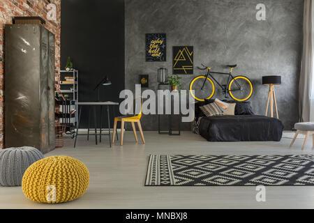 Appartement gris avec lit, bureau, chaise, mur de brique, jaune plus de détails Banque D'Images