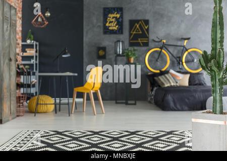 Hipster gris chambre avec lit, vélo, bureau et chaise jaune Banque D'Images