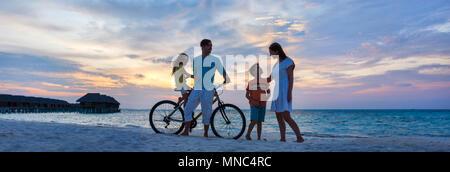 Famille avec un vélo sur la plage au coucher du soleil tropical, Panorama cousus Banque D'Images