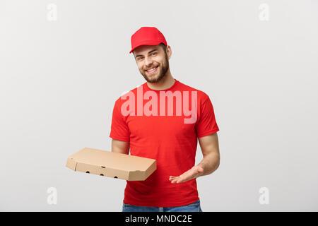 Concept de livraison: haapy young Handsome Pizza delivery man holding pizza box sur fond gris Banque D'Images